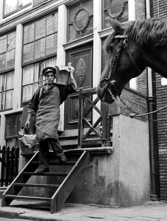 Een stronttonnetjesschepper heeft twee emmers met uitwerpselen opgehaald uit een huis in de Jordaan in Amsterdam, en begeeft zich weer naar zijn boldootkar. 13 september 1953.